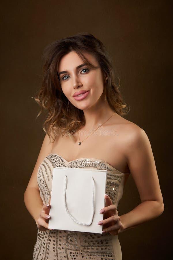 Retrato de la mujer hermosa joven con el bolso de compras contra fondo oscuro imagen de archivo libre de regalías