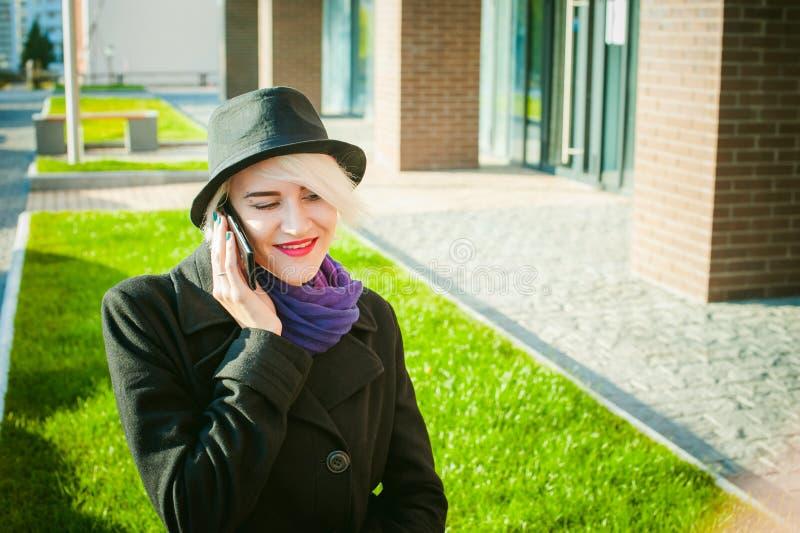 Retrato de la mujer hermosa joven con el pelo blanco, en una capa negra, una falda y un sombrero negro, hablando en el teléfono c imagen de archivo