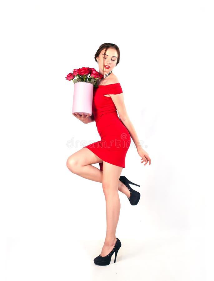 Retrato de la mujer hermosa joven con la caja de flores que presentan en estudio en crecimiento completo ramo de flores en caja d imágenes de archivo libres de regalías