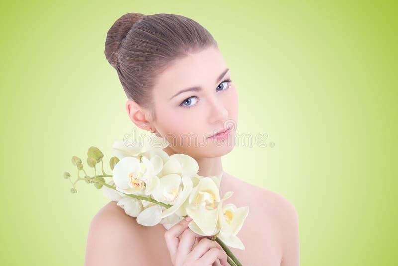 Retrato de la mujer hermosa joven con la flor de la orquídea sobre verde fotografía de archivo libre de regalías