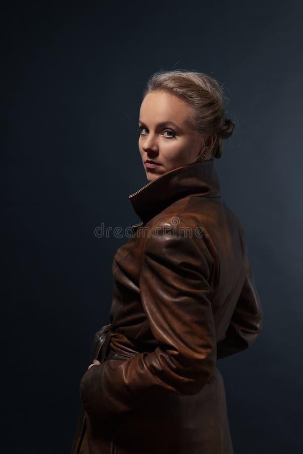 Retrato de la mujer hermosa joven en capa de cuero marrón fotos de archivo
