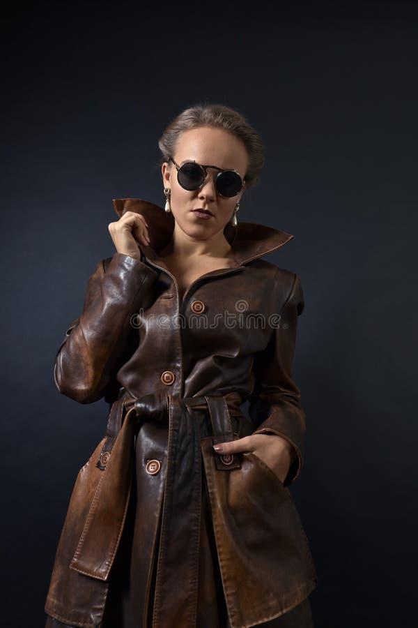 Retrato de la mujer hermosa joven en capa de cuero marrón imágenes de archivo libres de regalías