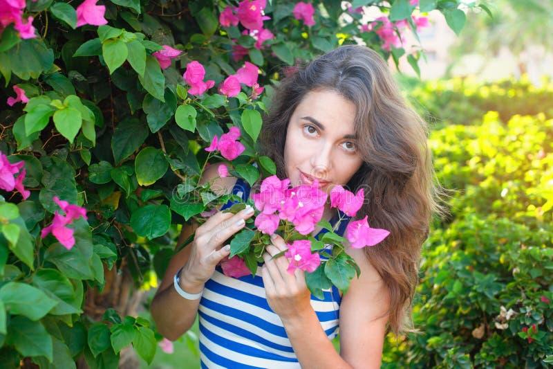 Retrato de la mujer hermosa joven en el fondo de las flores violetas púrpuras de la buganvilla en flor imagenes de archivo