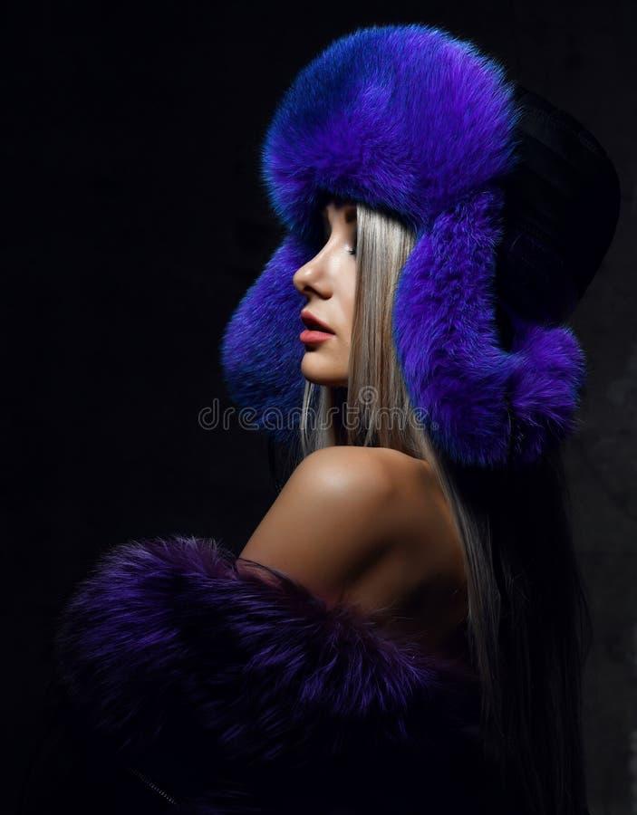 Retrato de la mujer hermosa joven en sombrero púrpura azul de la aleta del oído de la piel del invierno del zorro ártico de la mo foto de archivo libre de regalías