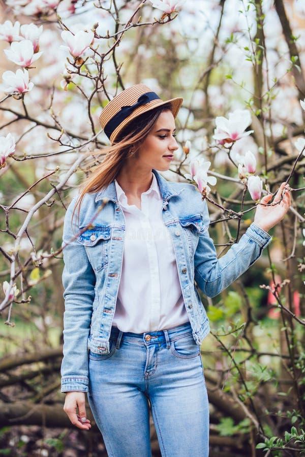 Retrato de la mujer hermosa joven en sombrero de paja en árboles del flor de la primavera fotos de archivo