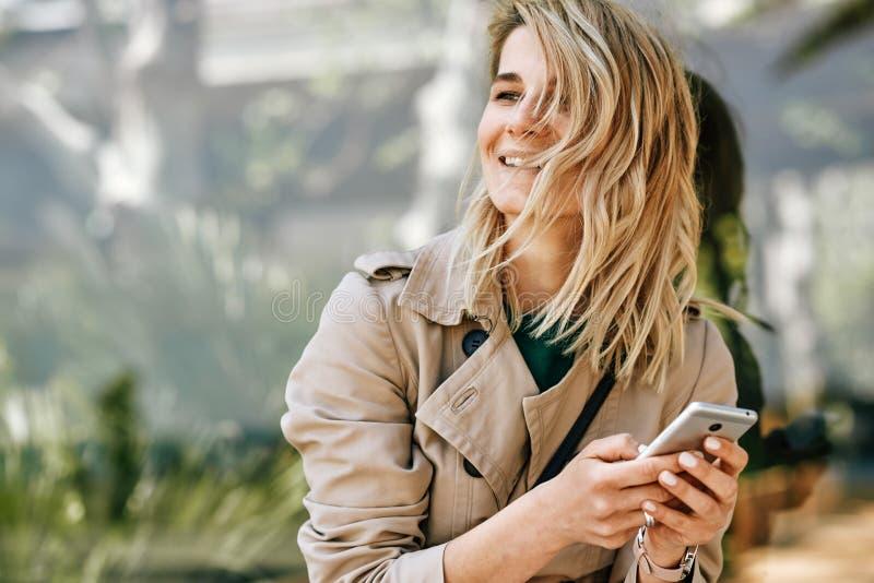 Retrato de la mujer hermosa joven feliz que sonríe y que considera lejos, usando el teléfono móvil, sentarse al aire libre en la  foto de archivo libre de regalías
