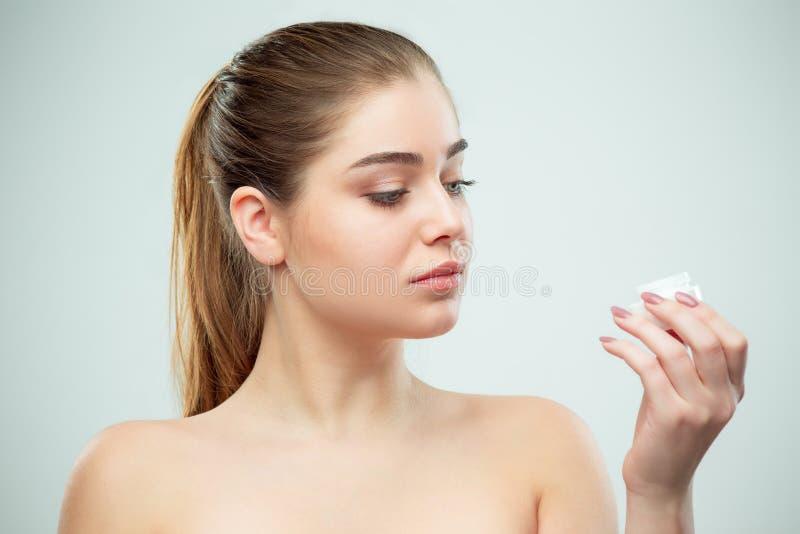 Retrato de la mujer hermosa joven que aplica la crema hidratante en su cara imágenes de archivo libres de regalías