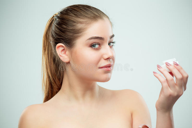 Retrato de la mujer hermosa joven que aplica la crema hidratante en su cara fotografía de archivo libre de regalías