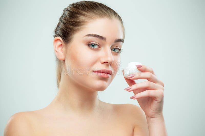 Retrato de la mujer hermosa joven que aplica la crema hidratante en su cara foto de archivo libre de regalías