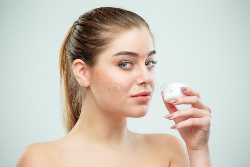 Retrato de la mujer hermosa joven que aplica la crema hidratante en su cara imagen de archivo