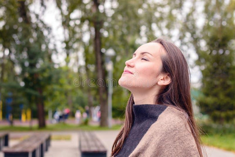 Retrato de la mujer hermosa joven que hace la respiración del aire fresco del otoño en un parque verde el concepto de aire atmosf imágenes de archivo libres de regalías