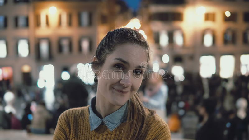 Retrato de la mujer hermosa joven que se coloca en el centro de ciudad por la tarde La muchacha del estudiante mira la cámara, so imágenes de archivo libres de regalías