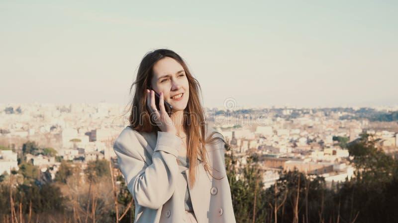 Retrato de la mujer hermosa joven que se coloca en la vista panorámica de Roma, Italia El hablar femenino en el smartphone imagenes de archivo