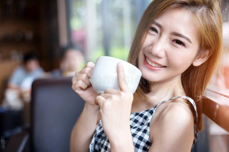 Retrato de la mujer hermosa joven que se sienta en un café foto de archivo libre de regalías