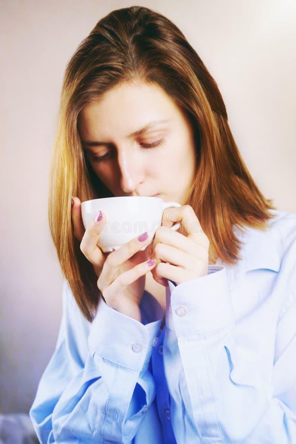 Retrato de la mujer hermosa joven que sorbe la bebida caliente en su cama foto de archivo libre de regalías