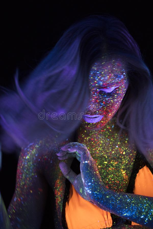Retrato de la mujer hermosa de la moda en la luz de neón del uF Girl modelo con el maquillaje psicodélico creativo fluorescente,  foto de archivo libre de regalías