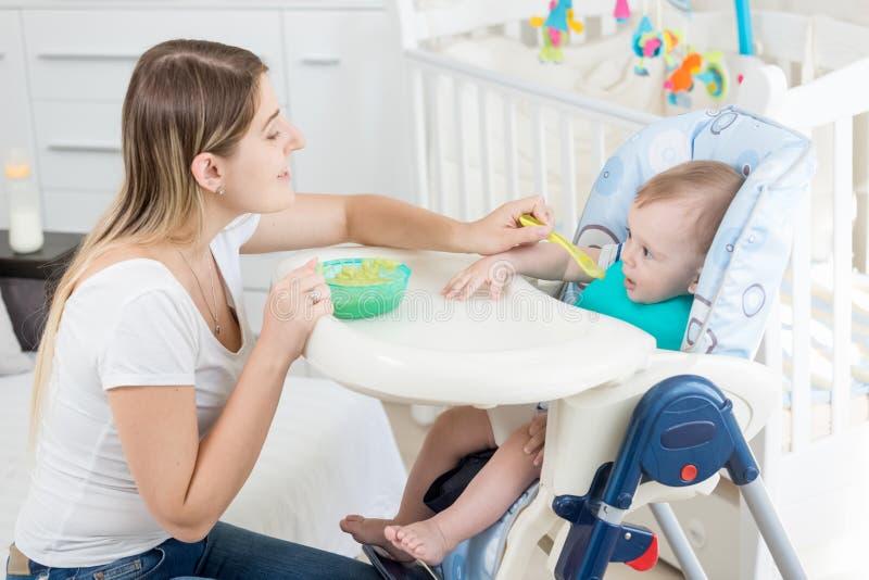 Retrato de la mujer hermosa que alimenta 9 meses del sittin del bebé fotos de archivo
