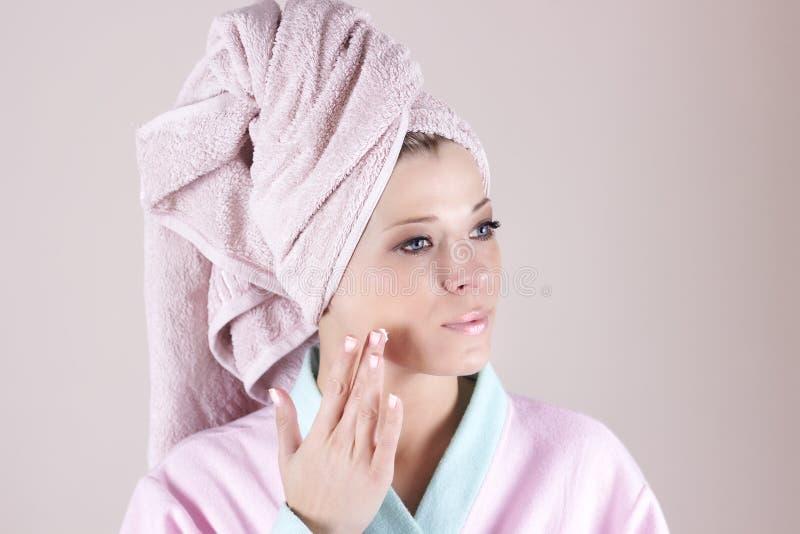 Retrato de la mujer hermosa que aplica la crema en cara foto de archivo libre de regalías