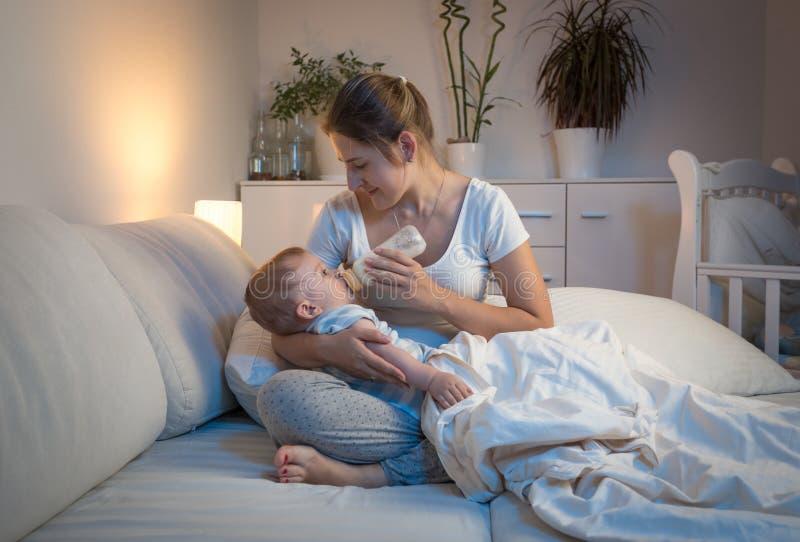 Retrato de la mujer hermosa que da la leche de la botella a su bebé foto de archivo
