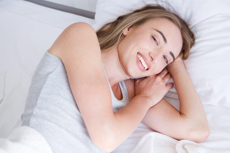 Retrato de la mujer hermosa que despierta en su cama blanca y que bosteza Resto, el dormir, gente y concepto de la comodidad imagenes de archivo