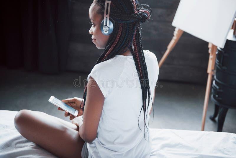 Retrato de la mujer hermosa que despierta en su cama y miradas en el teléfono Compruebe las redes sociales, envíe el SMS La mucha imágenes de archivo libres de regalías