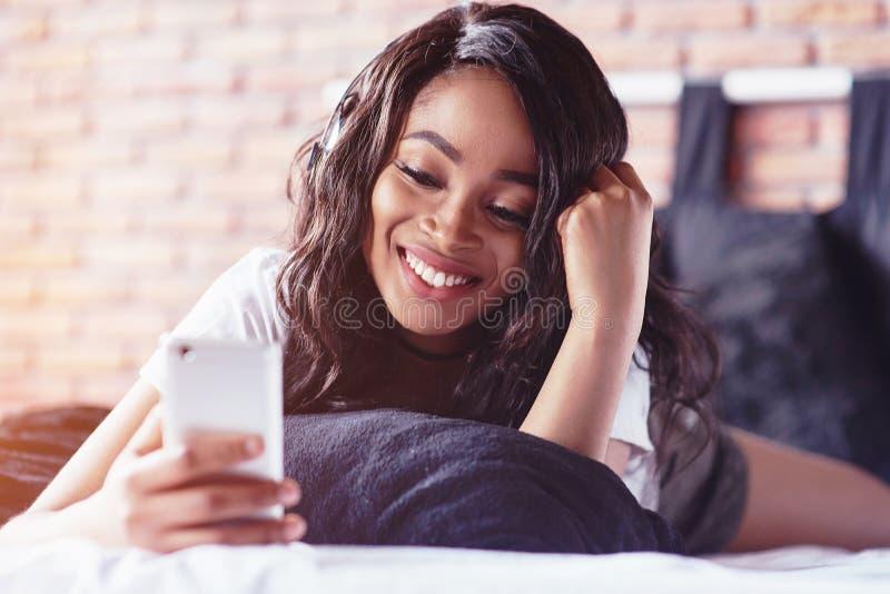 Retrato de la mujer hermosa que despierta en su cama y miradas en el teléfono Compruebe las redes sociales, envíe el SMS La mucha imagenes de archivo