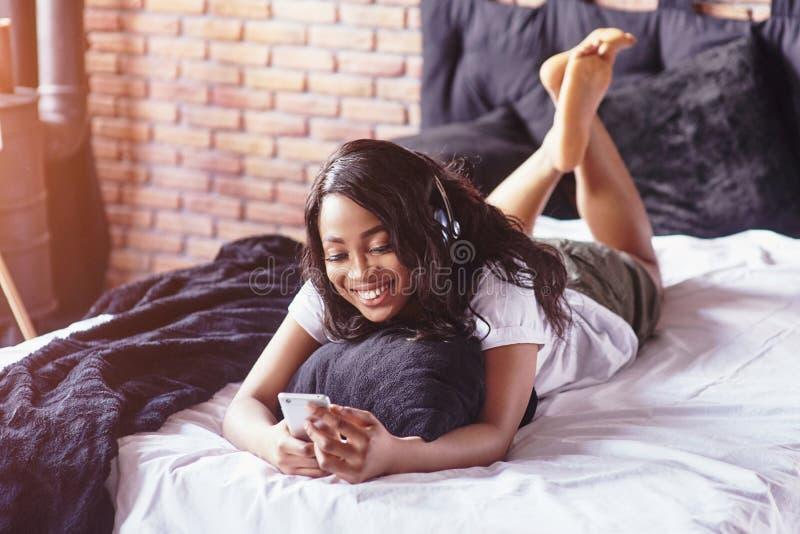 Retrato de la mujer hermosa que despierta en su cama y miradas en el teléfono Compruebe las redes sociales, envíe el SMS La mucha fotos de archivo libres de regalías