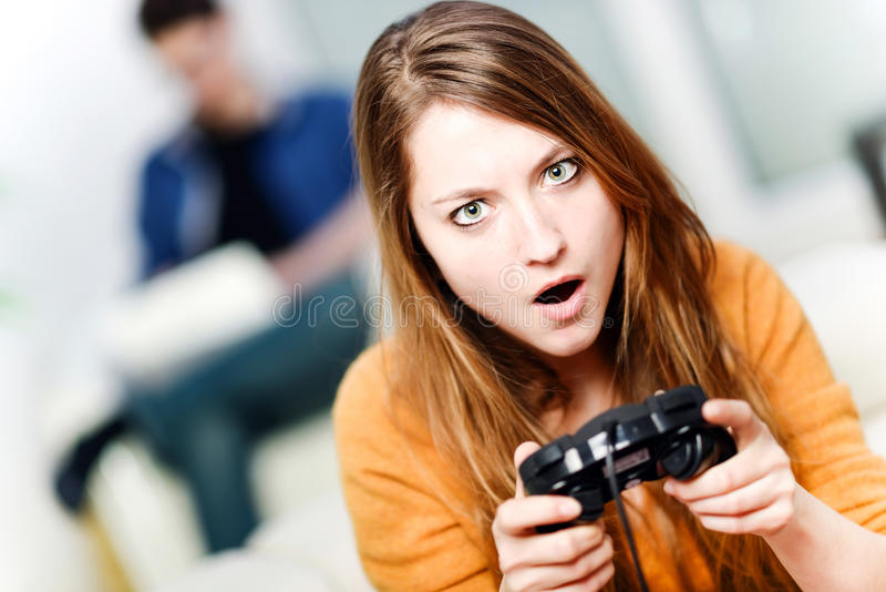 Retrato de la mujer hermosa que juega el videojuego en casa imagen de archivo libre de regalías