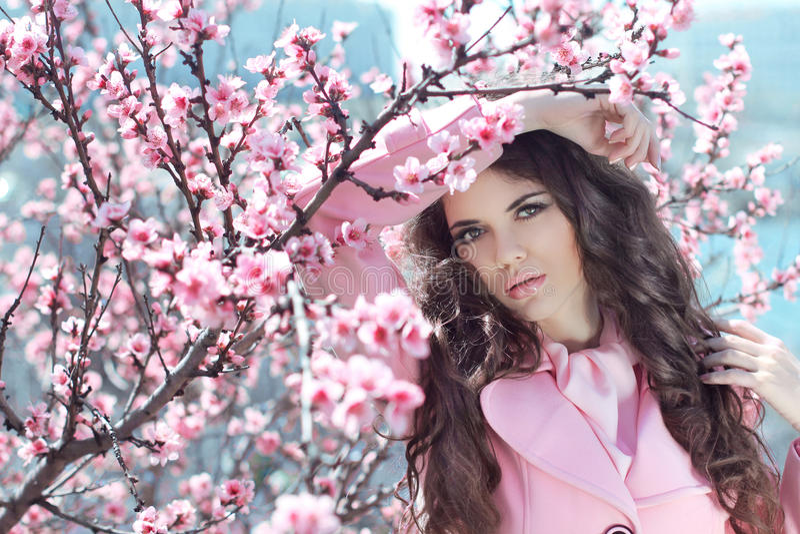 Retrato de la mujer hermosa que presenta sobre bloss rosados de la cereza de la primavera imagen de archivo
