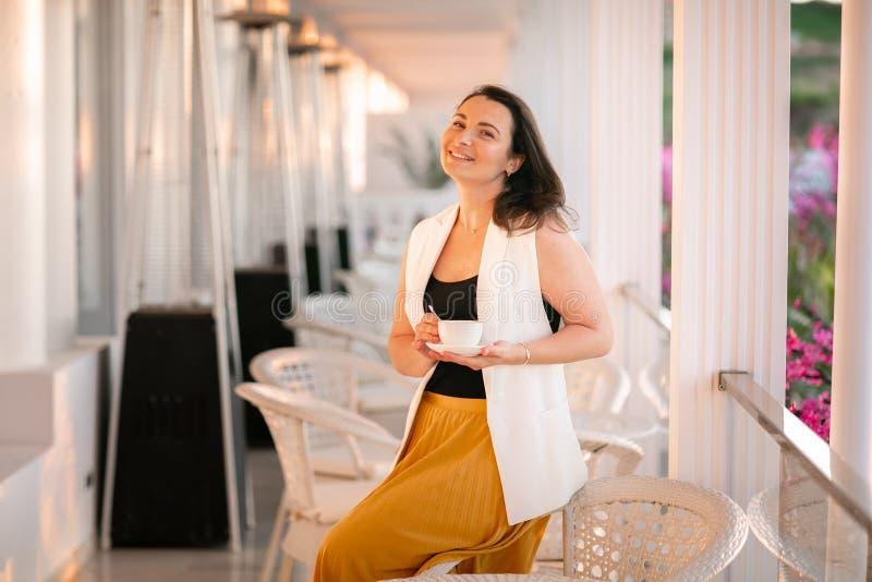Retrato de la mujer hermosa que se sienta en caf? del aire libre en Italia, caf? de consumici?n imágenes de archivo libres de regalías