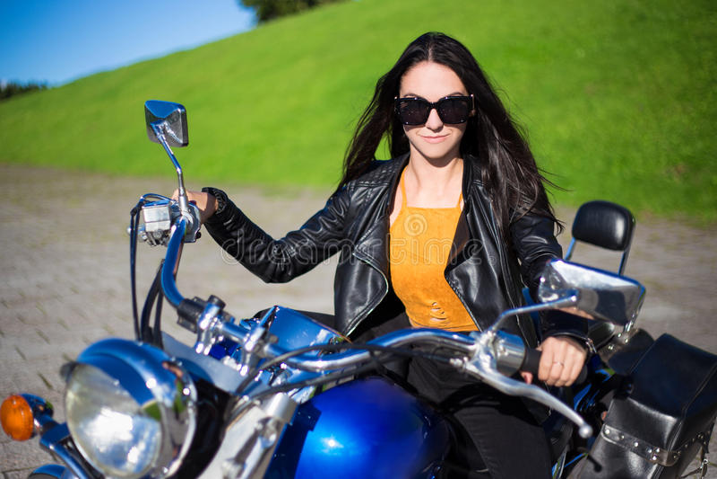 Retrato de la mujer hermosa que se sienta en la motocicleta retra foto de archivo libre de regalías
