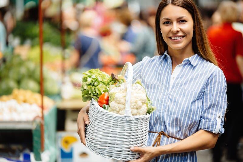 Retrato de la mujer hermosa que sostiene la cesta de compras foto de archivo