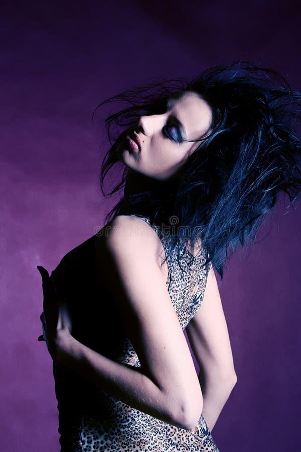 Retrato de la mujer hermosa sobre el fondo violeta imagen de archivo