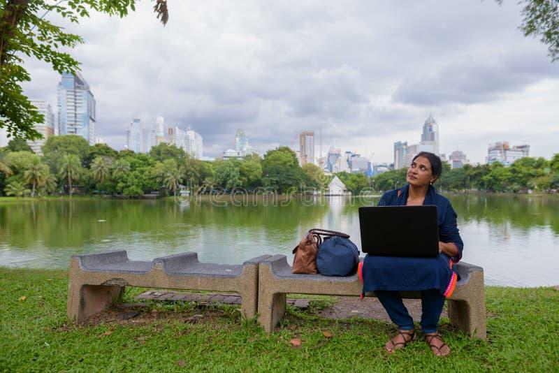 Retrato de la mujer india madura en el parque usando el ordenador portátil fotos de archivo libres de regalías