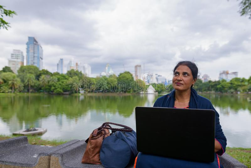 Retrato de la mujer india madura en el parque usando el ordenador portátil foto de archivo