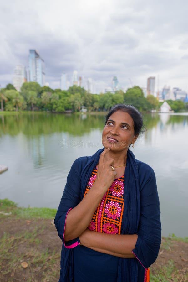 Retrato de la mujer india madura que piensa en el parque foto de archivo