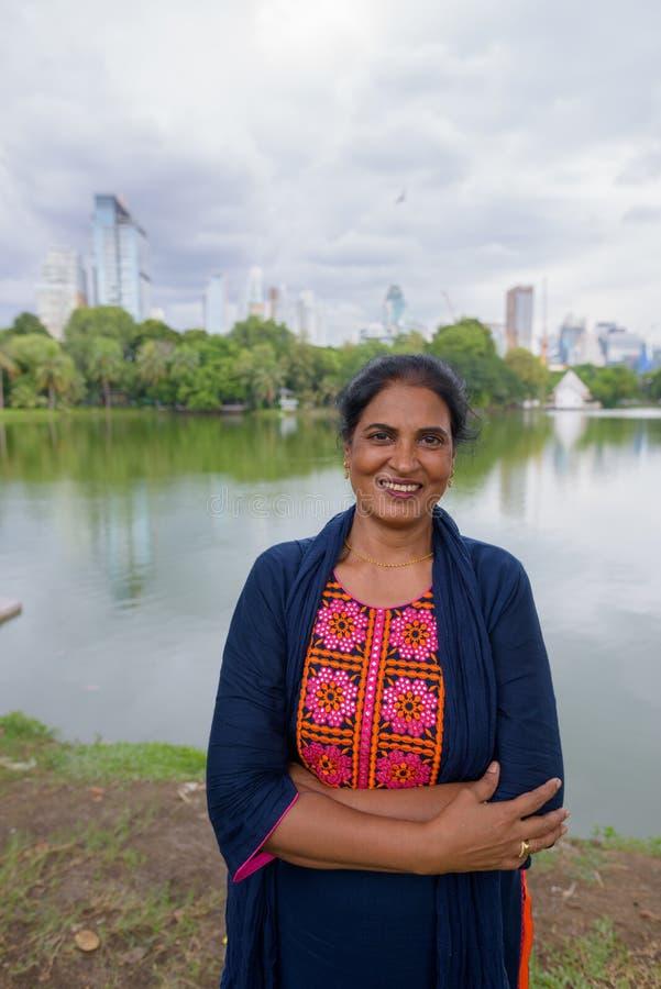 Retrato de la mujer india madura que sonríe en el parque imagenes de archivo