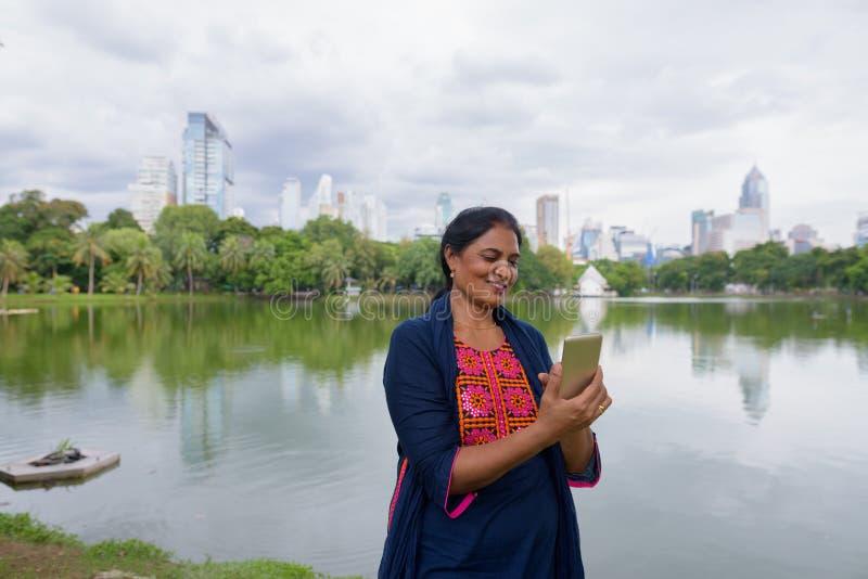 Retrato de la mujer india madura que usa el teléfono móvil en el parque fotografía de archivo