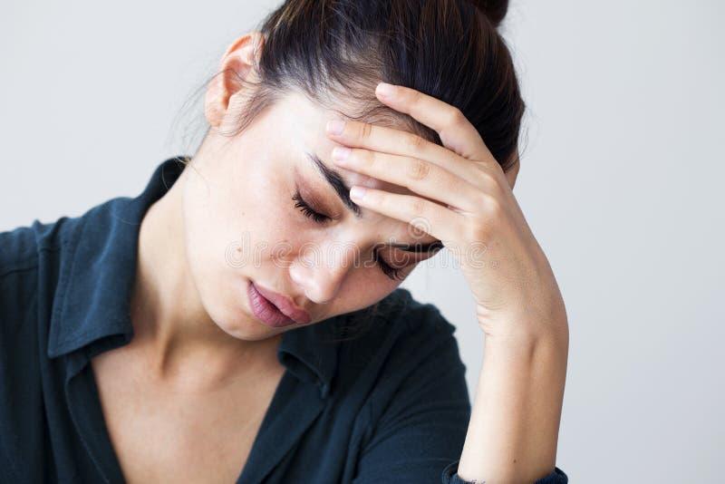 Retrato de la mujer infeliz en fondo gris foto de archivo