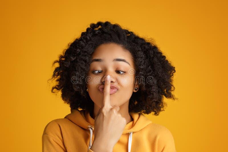 Retrato de la mujer joven afroamericana loca con sonrisa hermosa vestida en ropa casual sobre fondo amarillo fotografía de archivo libre de regalías