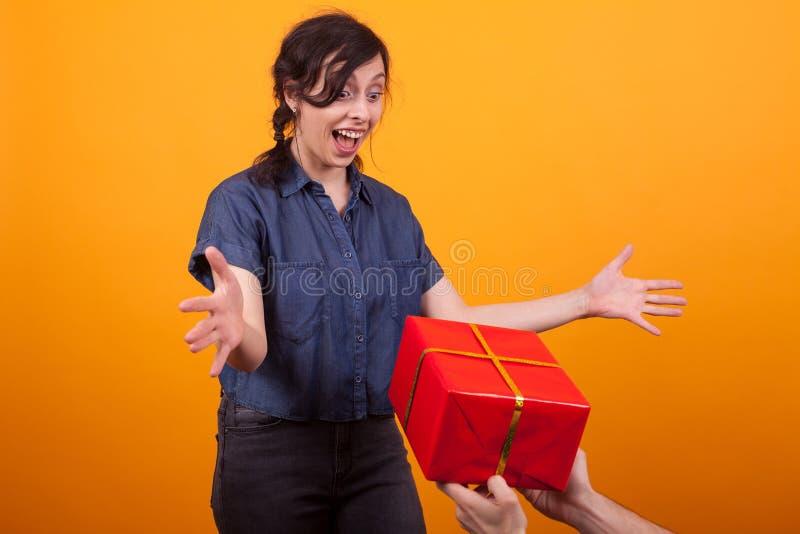 Retrato de la mujer joven alegre al ver una caja de regalo roja en estudio sobre fondo amarillo imagen de archivo