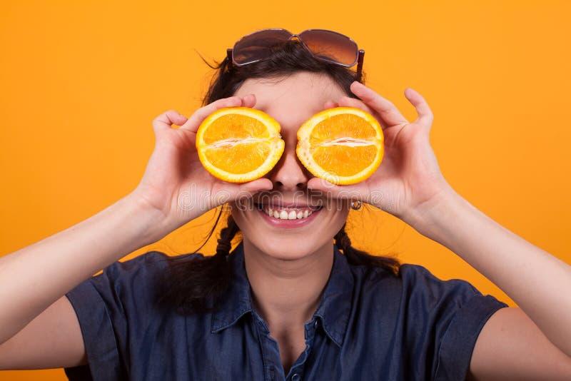 Retrato de la mujer joven alegre con la naranja cortada como ojos en estudio sobre fondo amarillo fotos de archivo libres de regalías