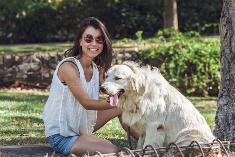 Retrato de la mujer joven alegre que se sienta con el perro en parque del verano fotos de archivo