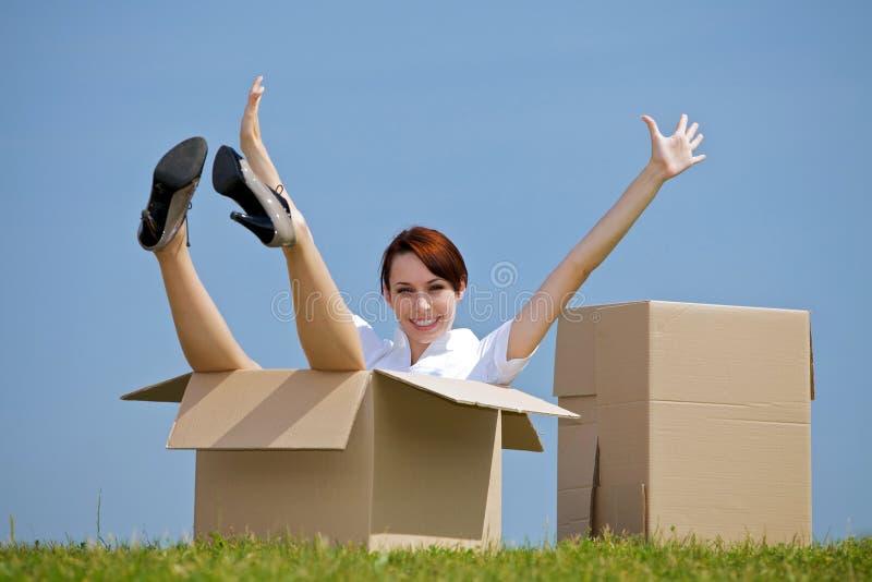 Retrato de la mujer joven alegre que se sienta en caja de cartón en el parque con los brazos extendidos imagen de archivo
