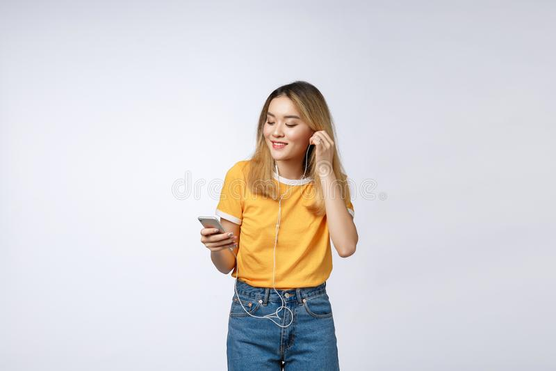 Retrato de la mujer joven asiática feliz escuchar la música con el auricular imagen de archivo