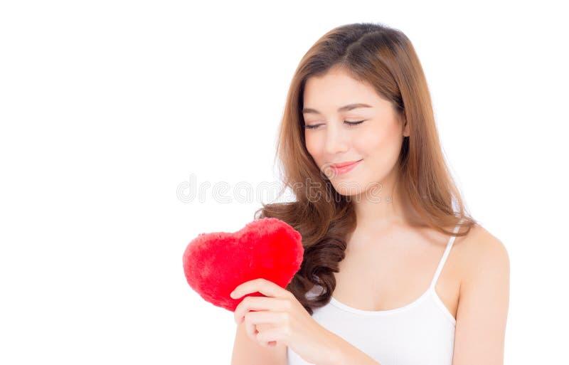 Retrato de la mujer joven asiática hermosa que celebra la almohada roja y la sonrisa de la forma del corazón aislado fotografía de archivo libre de regalías