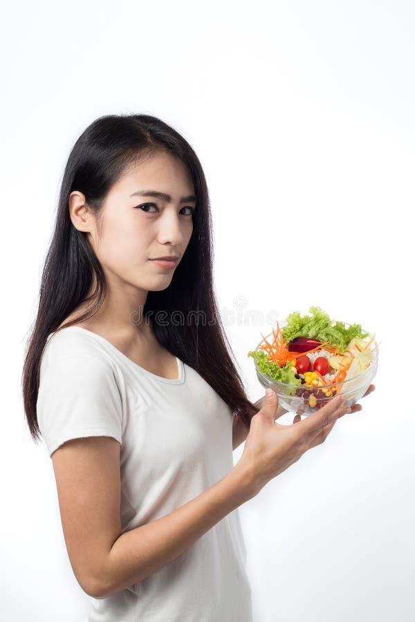 Retrato de la mujer joven asiática hermosa que come la ensalada vegetal fotos de archivo