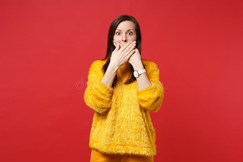 Retrato de la mujer joven asustada chocada en boca amarilla de la cubierta del suéter de la piel con las manos aisladas en la par fotografía de archivo