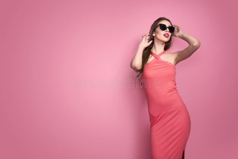 Retrato de la mujer joven atractiva delgada hermosa joven en vestido sexy con los labios sensuales rojos en fondo rosado en estud foto de archivo libre de regalías