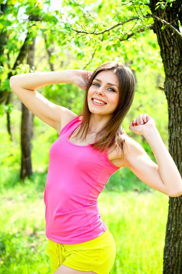 Retrato de la mujer joven atractiva en un parque del verano imágenes de archivo libres de regalías